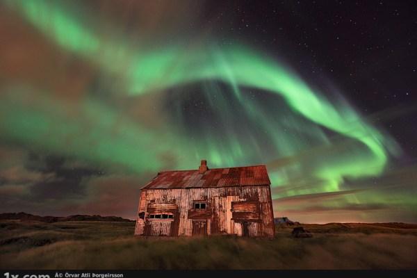 Green aurora over rusty shack