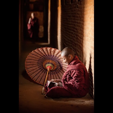 Buddhist monk reading a book and smiling
