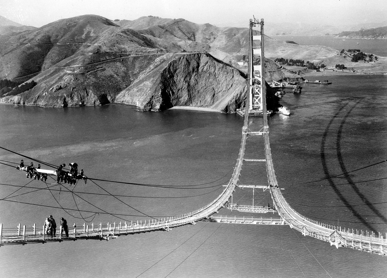 Workers complete the catwalks for the Golden Gate Bridge, hundreds of feet above the water, prior to spinning the bridge cables during construction in 1935