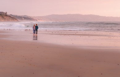 Couple taking a walk at Cardiff State Beach, San Diego County, CA.