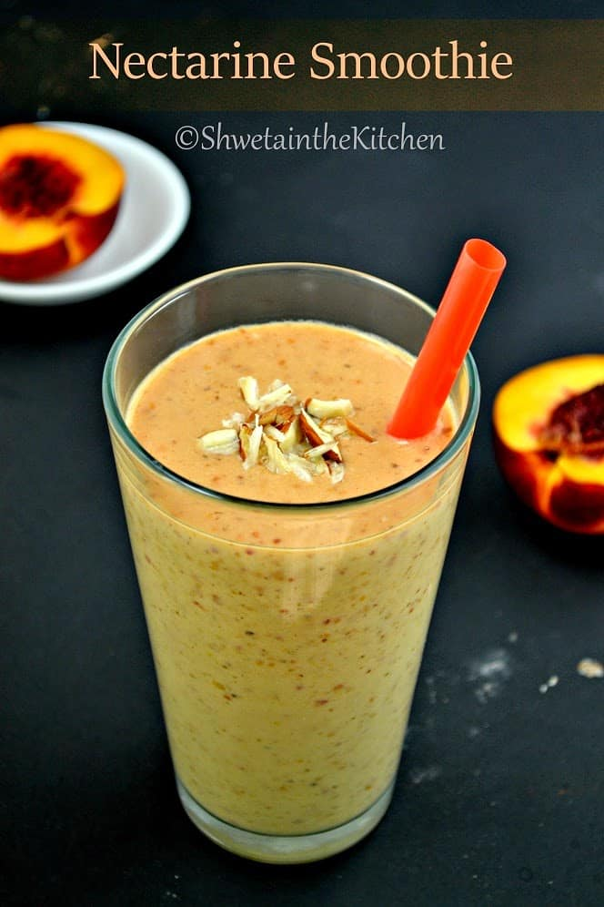 A nectarine smoothie in a glass with a straw and topped with almond pieces