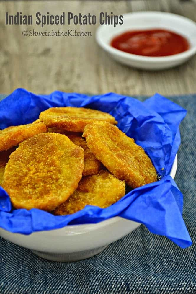 Indian spiced potato slices in a white bowl served with a tomato ketchup