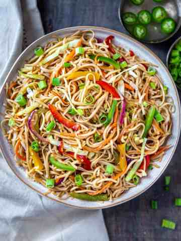 Bowl full of veg hakka noodles with green chillies soaked in vingear in background
