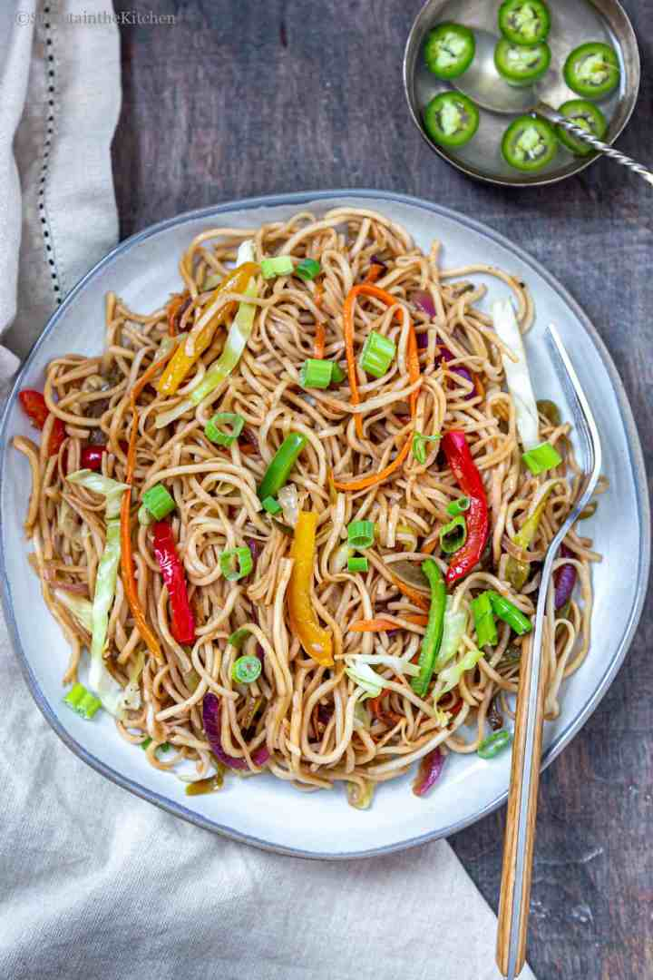 Vegetable hakka noodles on plate with fork on side and bowl of vinegar and chillies next to plate.