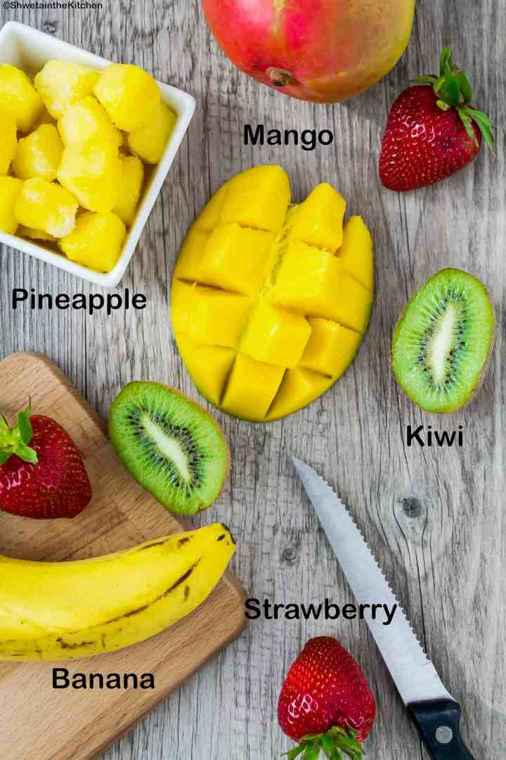 Top view of cut mango, kiwi, few strawberries, bowl of pineapple pieces and banana on cutting board