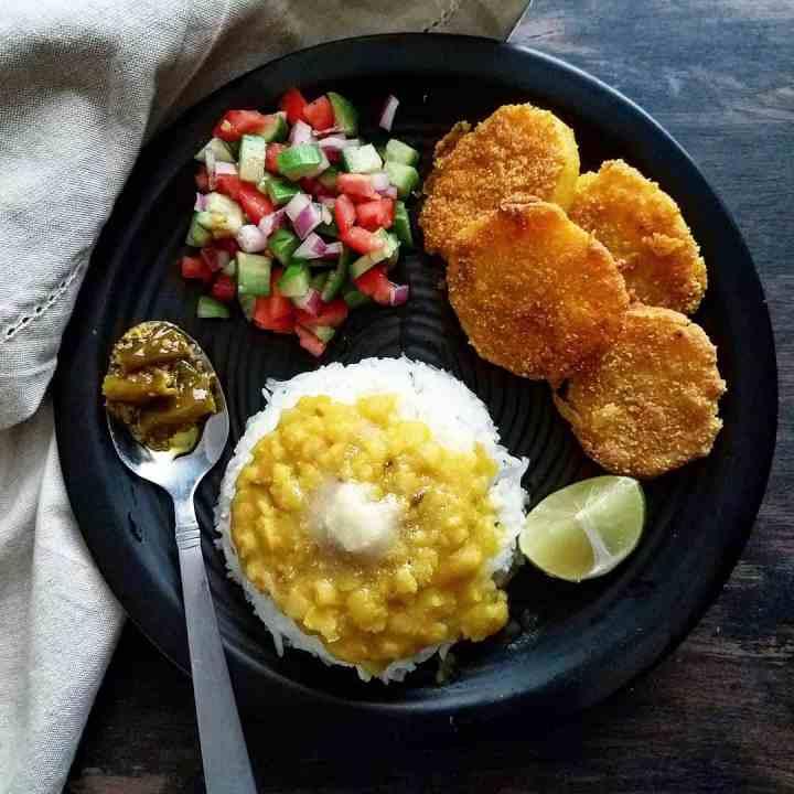 Black plate with varan bhaat, pickle, salad ,Batata Kaap, and lemon slice
