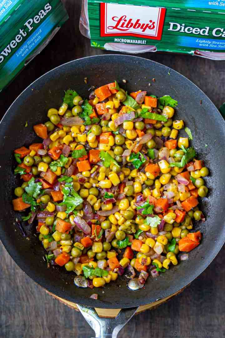 Pan of mix vegetable filling garnished with cilantro