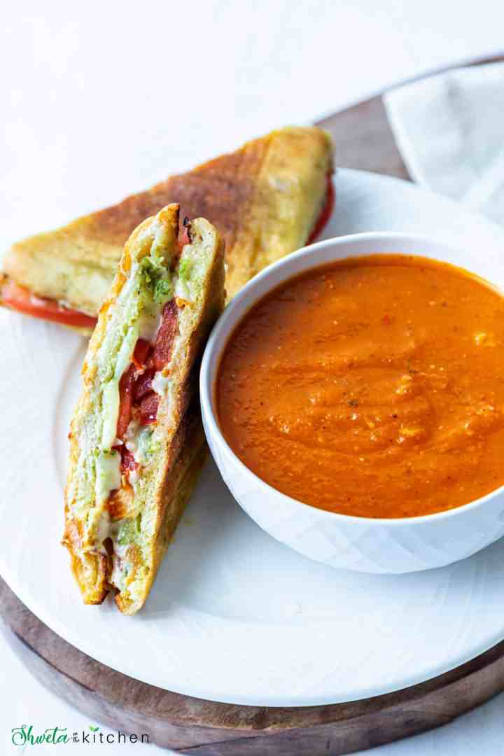 Tomato basil soup in a bowl with grilled cheese sandwich on side on a plate
