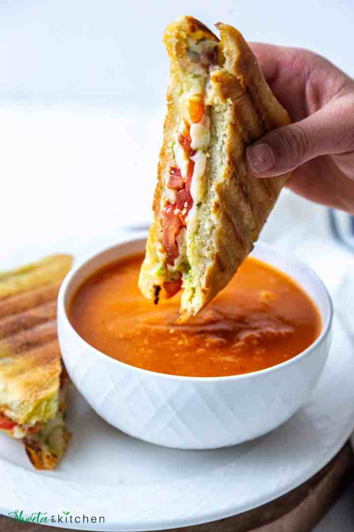 Grilled cheese sandwich about to be dunked in tomato basil soup