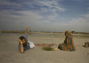 Shyamdas lounges by Yamuna in the company of a local farmer