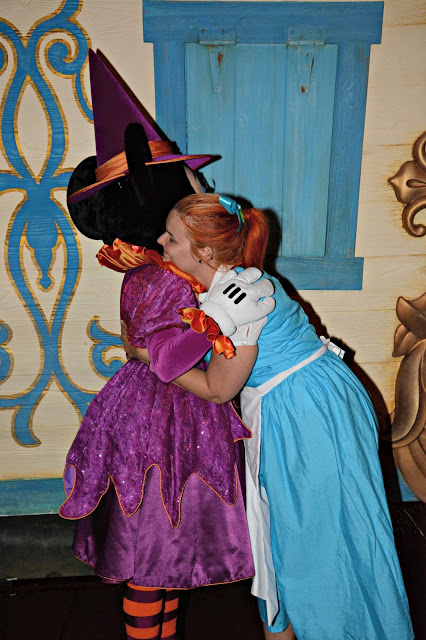women in Belle Costume hugging minnie mouse
