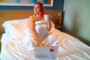 girl in a travelodge bed holding tea with a laptop in brighton