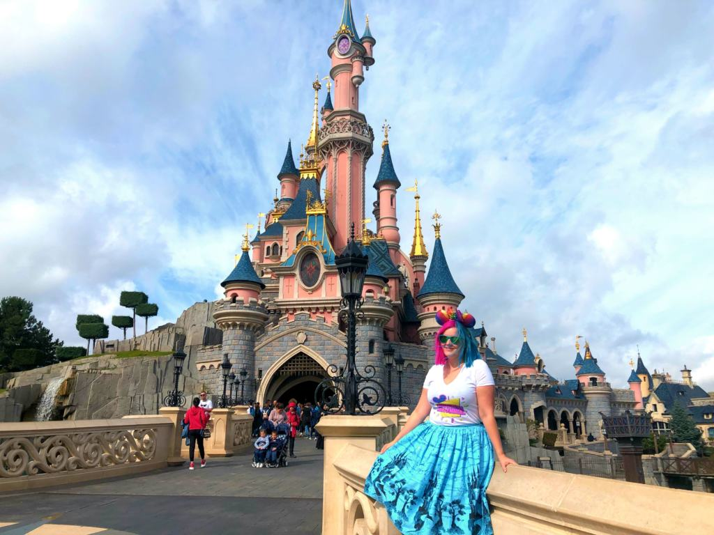 Kariss sitting in front of the castle on a cheap trip to Disneyland Paris