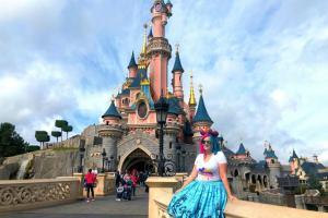 Kariss sitting in front of the castle in Disneyland Paris