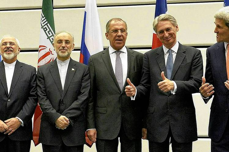 U.S. Secretary of State John Kerry, far right, and U.K. Foreign Secretary Philip Hammond, second from right, gesture toward Iran Foreign Minister Javad Zarif, far left. Iran's Ali Akbar Salehi is second from left. R