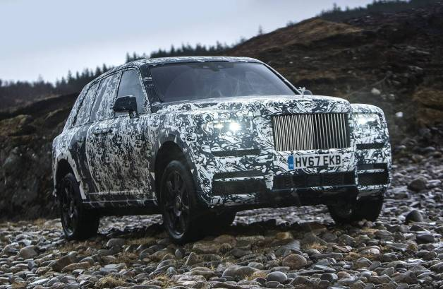 STATUS MONSTER Seen in this spy photo in a prerelease camouflage paint job, the 2019 Rolls-Royce Cullinan is estimated at more than 6 feet tall and 17 feet long.