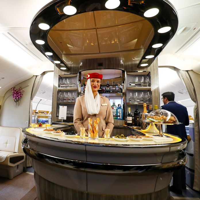 Emirates flight attendants in the bar area of a first-class cabin.