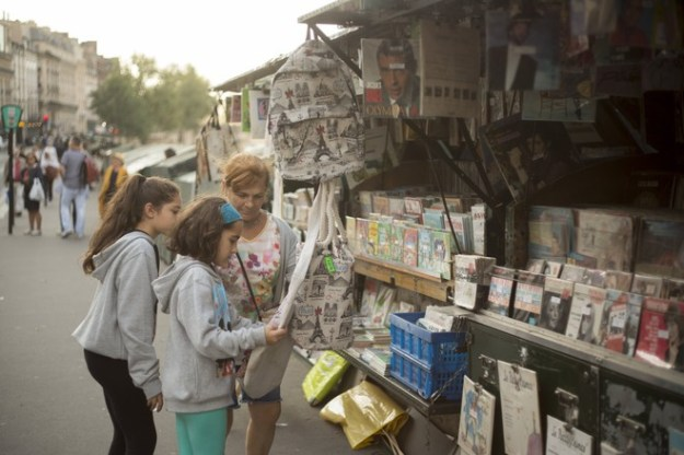 Tourists stop at a Left Bank bookstall featuring a variety of goods.