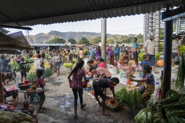 Locals sell fruits and vegetables in Dili, above. Below, people gather for the first Mass at a new church in Zumalai.