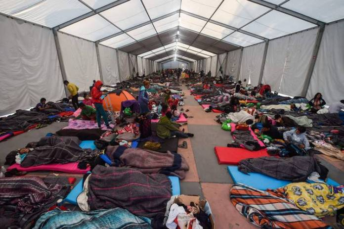 Exhausted migrants rested on tarps in huge tents set up by local officials.