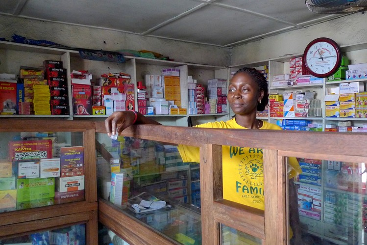 Pharmacist Doris Nyenkan takes money from a customer at her store in the West Point slum in Liberia's capital. She says that since the Ebola outbreak started she stands far back from her customers to avoid contact.