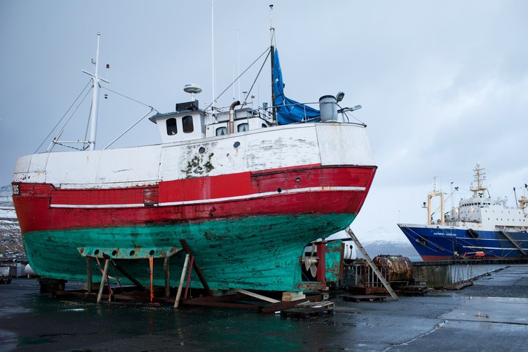 A fishing boat from the Faeroe Islands undergoes repairs while a Russian trawler floats in the background.