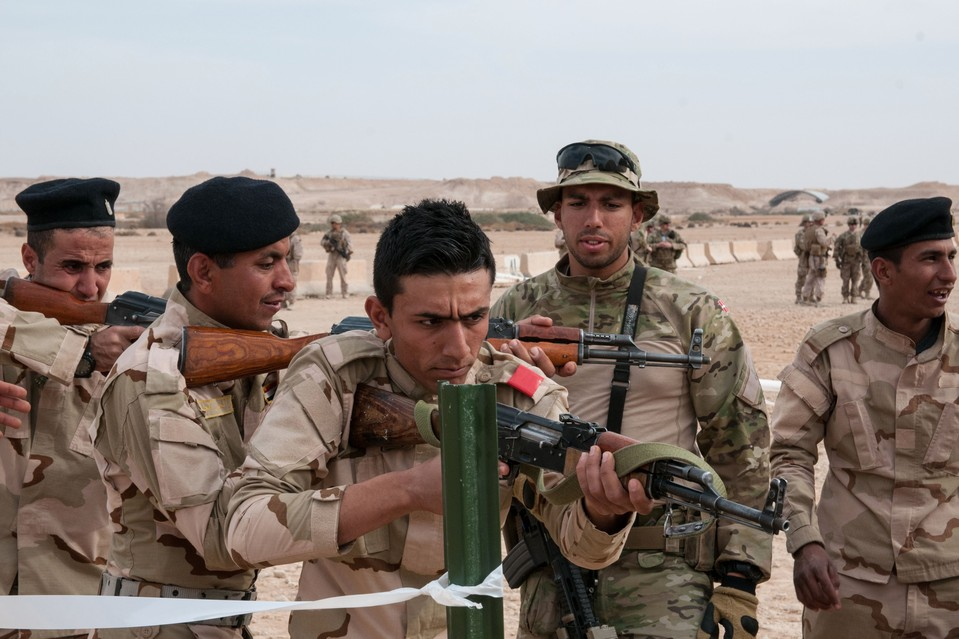 In this Feb. 10 photo released by the U.S. Army, a Danish trainer helps Iraqi army trainees as part of multinational efforts in helping combat Islamic State militants in Iraq.