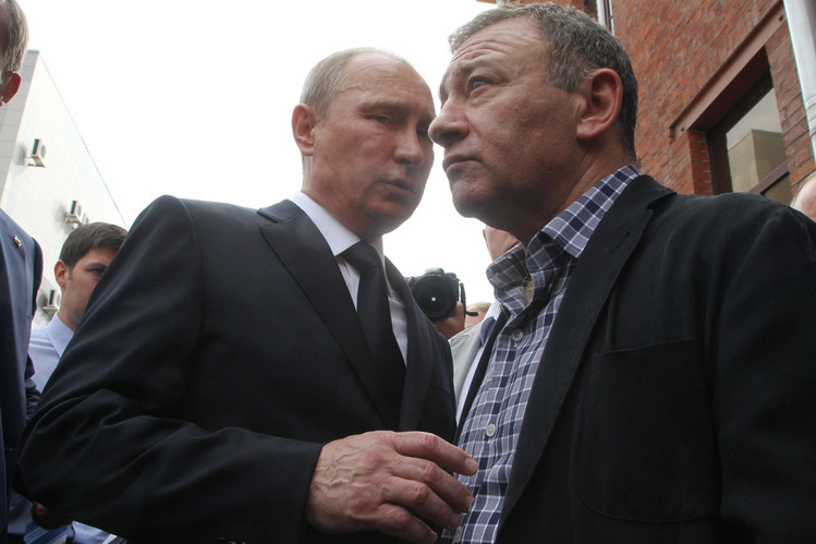 Russian President Vladimir Putin, left, and billionaire Arkady Rotenberg attend the funeral of a former judo trainer in St. Petersburg in 2013.