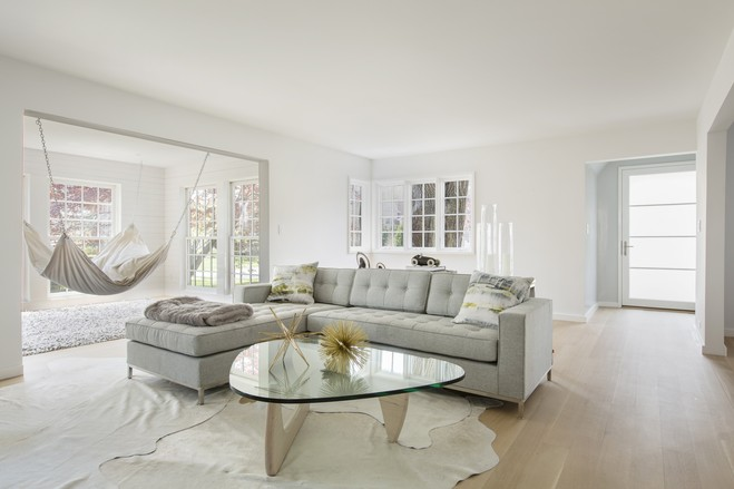 """The interior architecture throughout both the original rooms and the addition is contemporary, with little trim and sparse modern furnishings. Another shot of the living room and """"unsitting"""" room."""