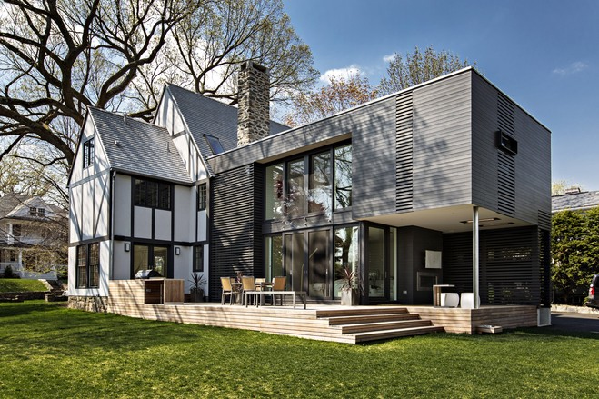 This glass-and-steel rectangular box is a modern addition to a 1920s Tudor home in Rye, N.Y. owned by Chris and Dana Perriello. Designed by Architect Joeb Moore, founder of the Greenwich, Conn. architectural firm Joeb Moore & Partners and a professor of architecture at both Barnard/Columbia and Yale, it is clad in charcoal colored stained cedar and juts out from the rear, with slatted wood walls and floor-to-ceiling glass windows.