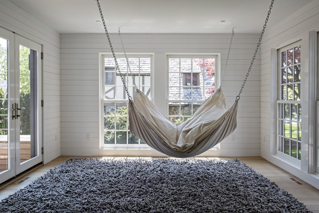 What had been a sitting room is now empty except for a big white Le Beanock hammock hanging from the ceiling over a shaggy gray rug. The family calls this the 'unsitting room'.