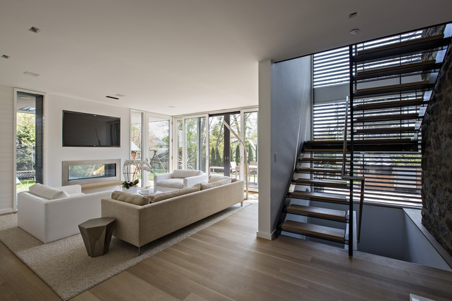 The steel-and-glass stairway acts as a transition between the original home (the end of which is demarked by the original exterior stone wall, which is now enclosed inside) to the addition, which includes this family room.