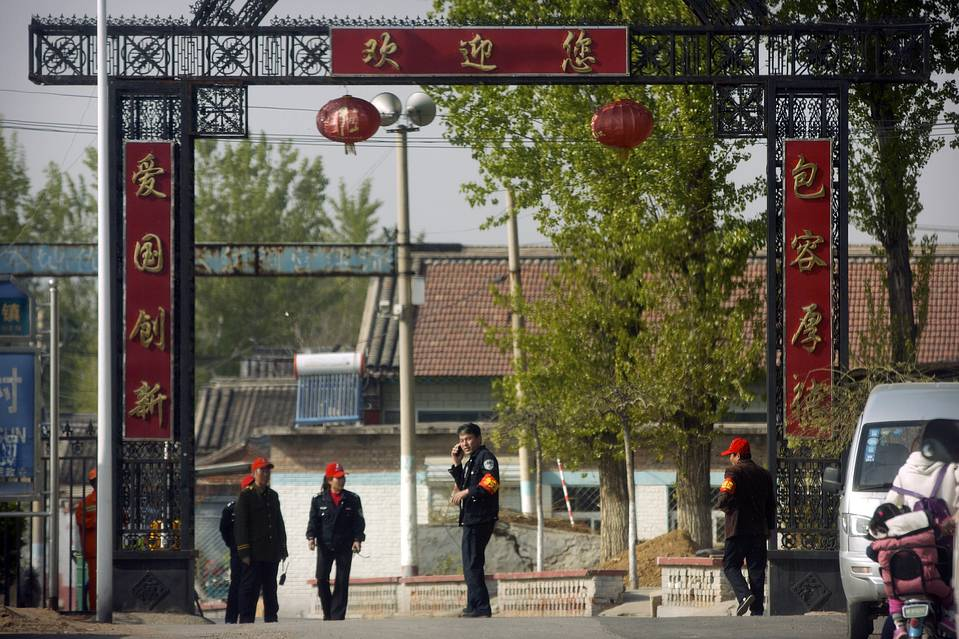 Chinese security officials stood guard in April at the entrance of Hongtongying village on the outskirts of Beijing where freed feminist activist Li Tingting is staying. Ms Li and four other recently released Chinese feminists say they are still being treated as criminal suspects.