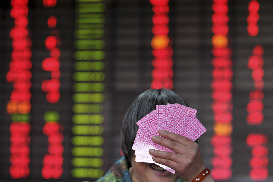 An investor covers her face with playing cards in front of an electronic stock information board at a brokerage house in Nanjing. The absence of a reassuring public face to China's rescue efforts has been felt by investors.