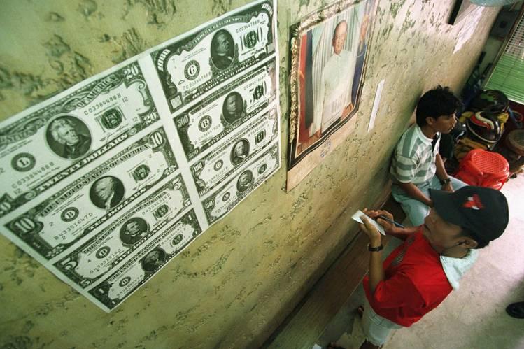 Uma casa de câmbio nas Filipinas mostra a cotação do dólar em outras moedas. A alta do dólar está tornando mais difícil para as empresas pagar dívidas na moeda americana.