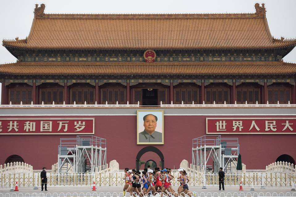 Athletes run past a portrait of Mao Zedong in Beijing. China has placed a cap on local government debt as it struggles with one of the biggest impediments to growth.