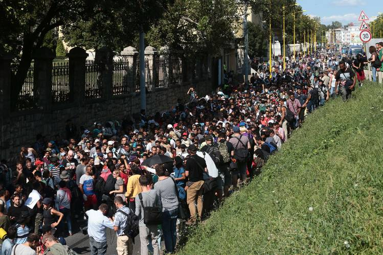 Hundreds of migrants leave the transit zone of the Budapest main train station.