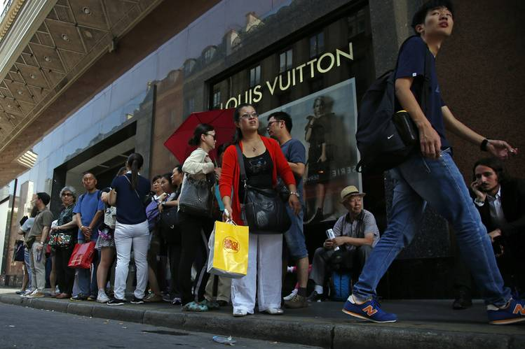 Chinese tourists waiting for their bus in front of a Louis Vuitton store in Paris in August.