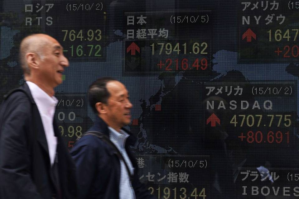 People walk past a board displaying key indexes of stock exchanges in front of a securities company in Tokyo on Monday. Global stock markets rose Monday as investors considered the prospect of U.S. interest rates remaining low for longer.