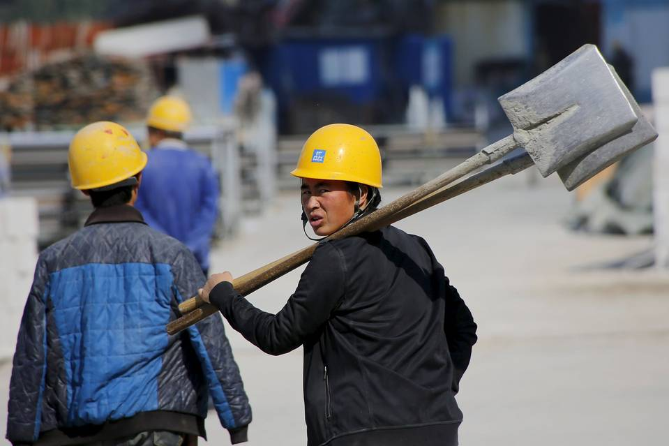 Workers passed by a Beijing construction site Thursday.