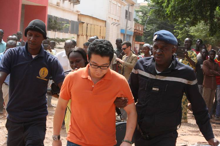 Police escort a Chinese hostage in Bamako, Mali, where three Chinese rail executives were killed during a hotel siege.
