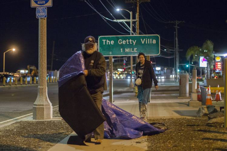 Jesse Mark Littlefield, left, with help from a homeless friend, Jessica, shifts his temporary encampment after a city worker ordered him to move on Wednesday in the Pacific Palisades neighborhood of Los Angeles.