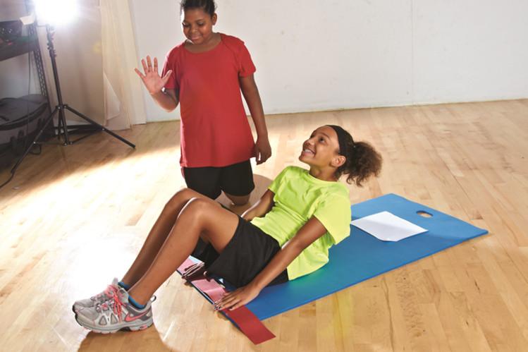 体力測定でカールアップをする女子児童