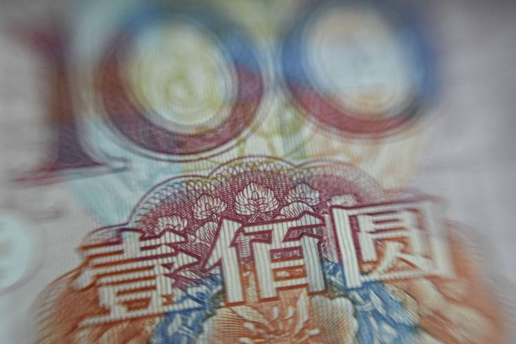 This photo illustration shows a Chinese 100-yuan note in Beijing in August.