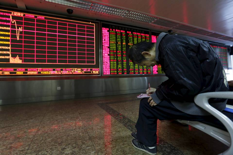 An investor takes notes of stock information Friday in front of an electronic board at a brokerage house in Beijing.