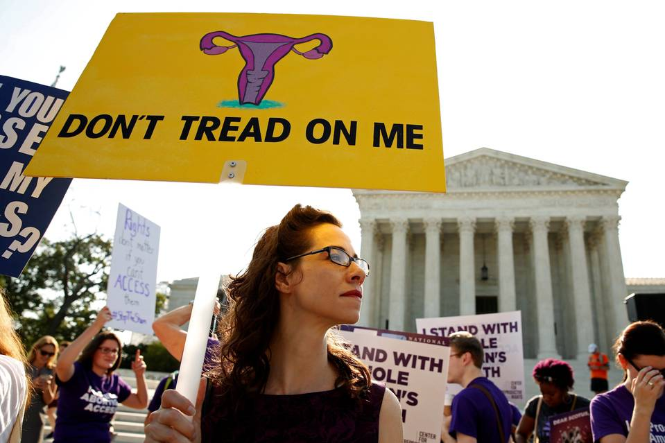 Demonstrators stand outside the U.S. Supreme Court in Washington on June 27.