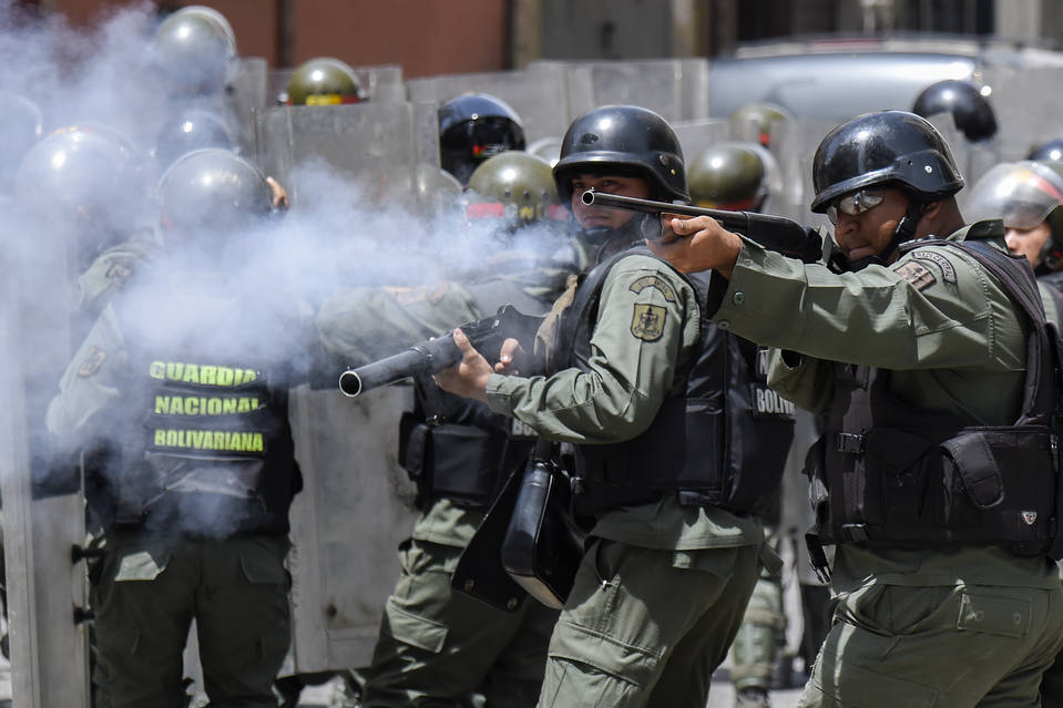 Security forces clash with people trying to reach Venezuela's presidential palace to protest against the severe food and medicine shortages in Caracas in June.
