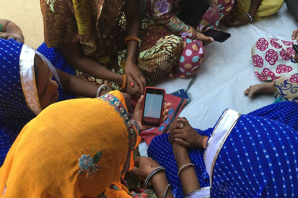 Women look at cell phones as part of Internet Saathi, the joint program of Alphabet, Inc.'s Google and local philanthropy Tata Trusts, in the village of Habibwala, in Rajastan, India, Sept. 28, 2016.