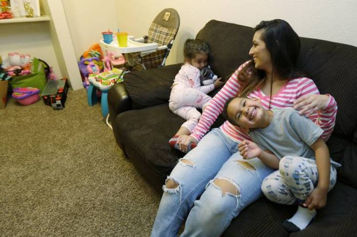 In Washington state, voters approved a minimum-wage increase. Above, Danielle Mendoza, who works as a cashier in a grocery store, with two of her three children in Renton, Wash.