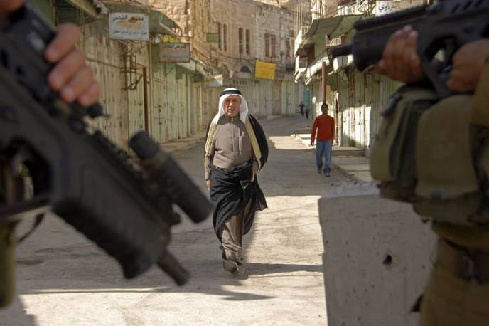 Israeli soldiers on guard as Palestinians pass by in the West Bank city of Hebron, Oct. 19, 2007. Some 800 Jewish settlers live in Hebron, tightly guarded by Israeli soldiers.